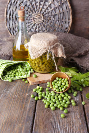 canned peas: Fresh  and canned peas in bowl and glass jar on napkin, on wooden background