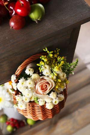 Basket of flowers hanging on wooden shelf close up photo