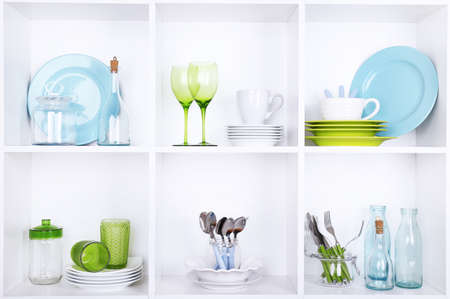 Kitchen utensils and tableware on beautiful white shelves Stock Photo