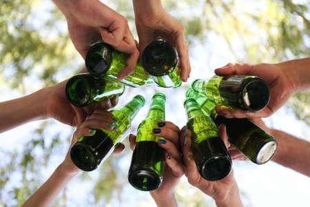 jovenes tomando alcohol: Manos que sostienen las botellas de cerveza, de cerca Foto de archivo