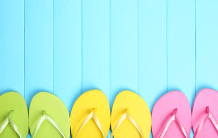 flops: Bright flip flops on wooden background
