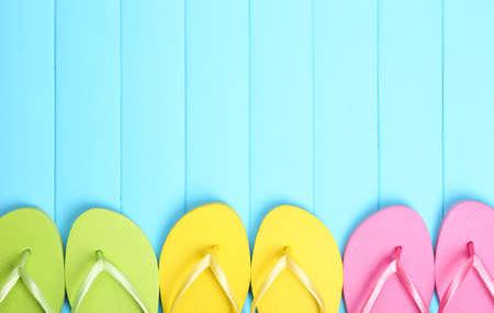 Bright flip flops on wooden background photo
