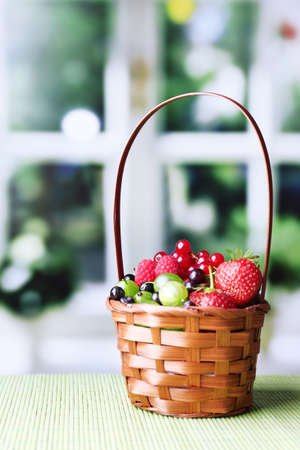 Forest berries in wicker basket, on wooden table, on bright background photo