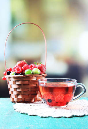 Forest berries in wicker basket and glass cup with red fruit tea, on wooden table, on bright background photo