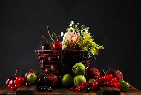 Still life with berries and flowers on dark background photo