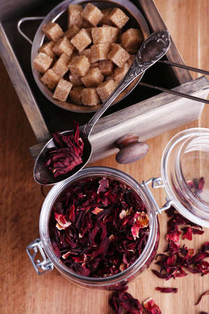 Dried hibiscus tea in glass jar, brown sugar  in box on wooden background photo