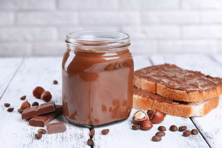 Sweet chocolate cream in jar on table on light background photo
