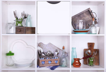 Kitchen utensils and tableware on beautiful white shelves photo