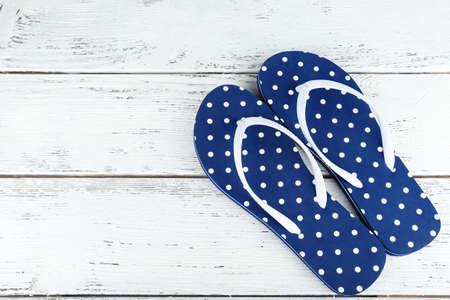 Color flip-flops on wooden background photo