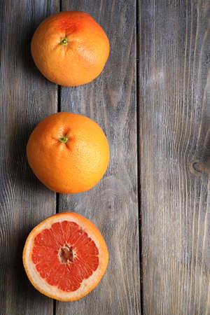 Ripe grapefruits on wooden background photo