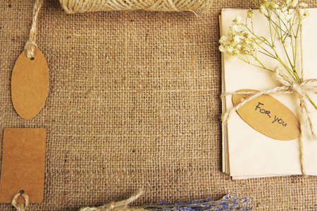 Natural style handcrafted gift box on sackcloth background. Concept of natural style design photo
