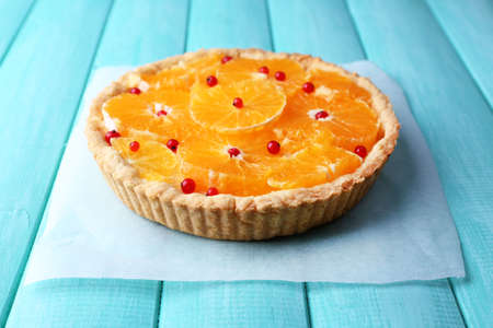 Homemade orange tart on color wooden background photo