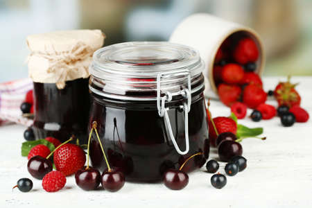 Tasty jam with berries in glass jars on wooden table photo