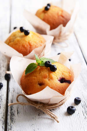 Tasty cupcakes with blueberries on table close-up photo