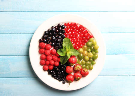 Forest berries on plate, on color wooden background photo