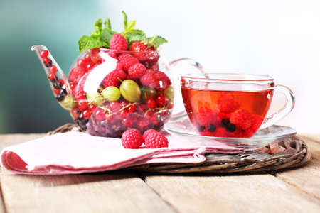 Fruit red tea with wild berries in glass cup, on wooden table, on bright background photo