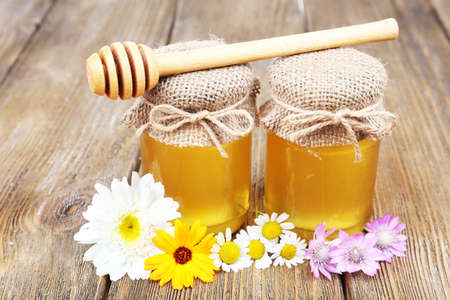 Jar full of delicious fresh honey and wild flowers on wooden table photo