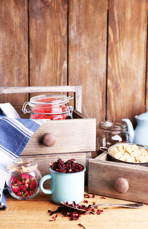 Dried hibiscus tea in color mug, brown sugar  in box on wooden background photo