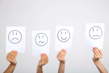 smileys: Hands holding up different smileys on grey background