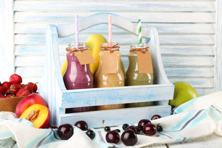 Bottles of delicious smoothie in wooden basket on table, close-up photo