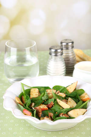 Green salad with spinach, apples, walnuts and cheese  table, on bright background photo