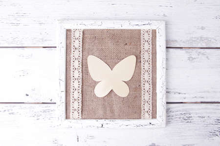 Wooden frame with paper butterfly isolated on white photo