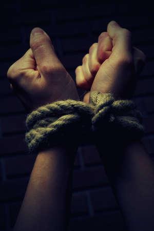 Tied hands on dark background photo