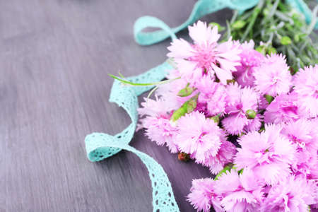 Beautiful bouquet with lace ribbon on wooden background photo