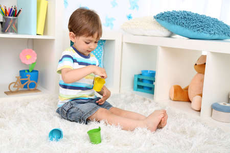 Cute little boy playing in room photo