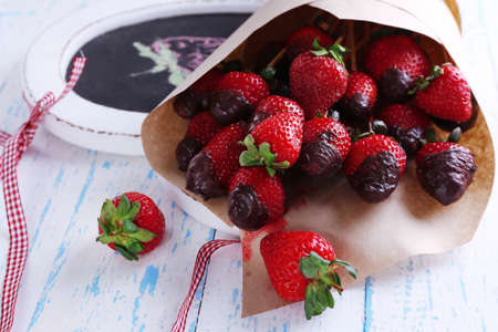 secular: Strawberry in chocolate on skewers in paper bag on table close-up