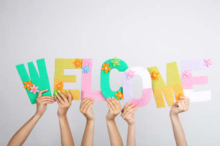 Hands holding up letters building word welcome on grey background Stock Photo