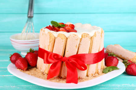 Tasty cake Charlotte with fresh strawberries on wooden table photo