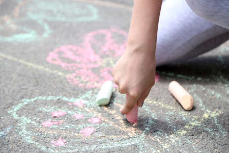 Girl drawing with chalk on asphalt