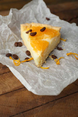 orange tart: Piece of homemade orange tart on paper napkin, on color wooden background