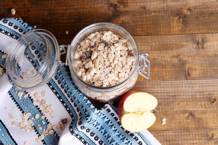 Homemade granola in glass jar, jugs with milk and fresh apple, on color wooden background photo