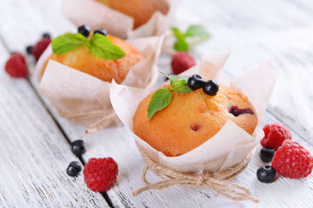 Tasty cupcakes with fruits on table close-up photo