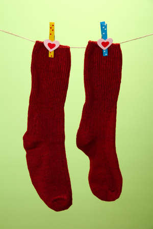 Colorful socks hanging on clothesline, on color background photo