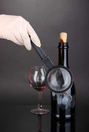 Taking fingerprints with bottle of wine isolated on black photo