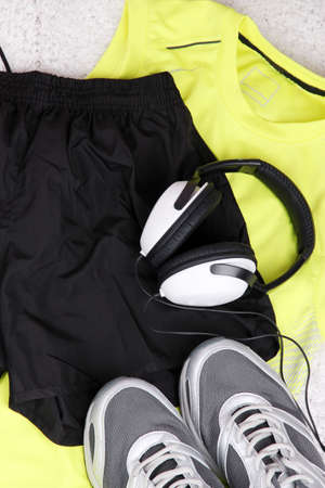 Sport clothes, shoes and headphones on white carpet background.  photo