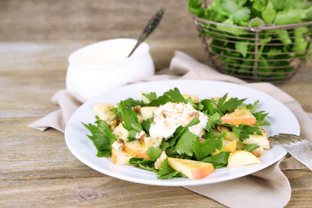 Green salad with apples, walnuts and cheese on wooden background photo