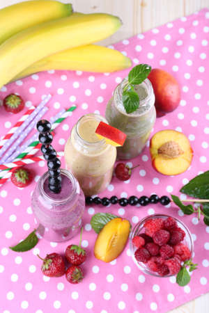 Bottles of delicious smoothie on table, close-up photo