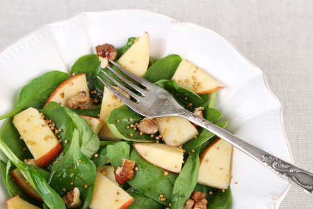 Green salad with spinach, apples, walnuts and cheese on light background photo