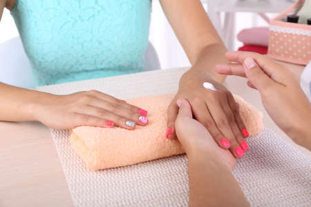 Young woman is getting manicure in beauty salon, close-up photo