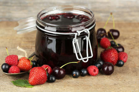 Tasty jam with berries in glass jar on wooden table photo