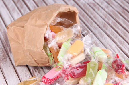 Tasty candies in paper bag on wooden background photo