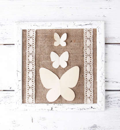 Wooden frame with paper butterflies isolated on white photo