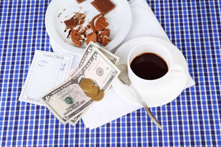 Check, money and remnants of food and drink on table close-up photo