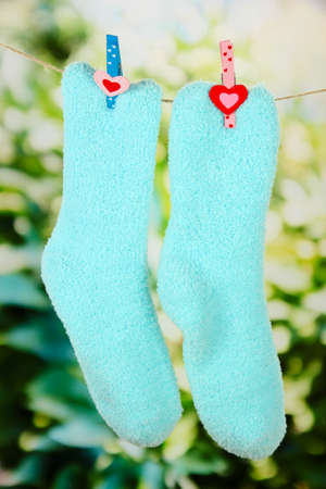 Colorful socks hanging on clothesline, on bright background photo