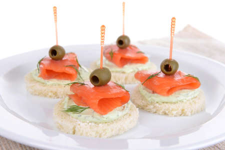 Delicious canapes on plate close-up photo