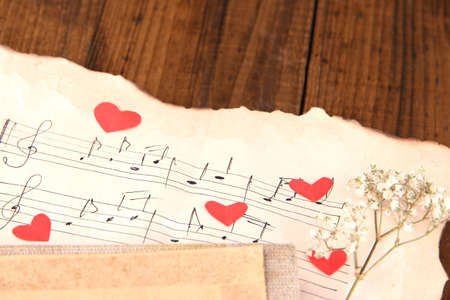 Dried rose flower on music book, close-up, on wooden background photo